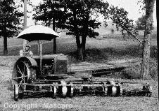 Steel wheel agricultural tractor with traction mower in front.