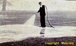 "Application of ""worm eradicating fertilizer to golf green"".  1920's."
