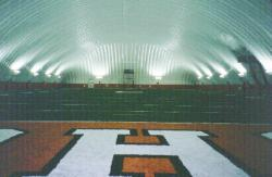 Southwest Texas University in San Marcos, TX also had an indoor practice field in an inflatable dome.  The surface is artificial turf (Astro Play) with two inches of crumb rubber topdressing mixed in with the fibers.